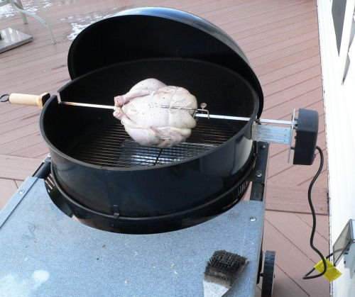 Rotisserie chicken on a charcoal grill