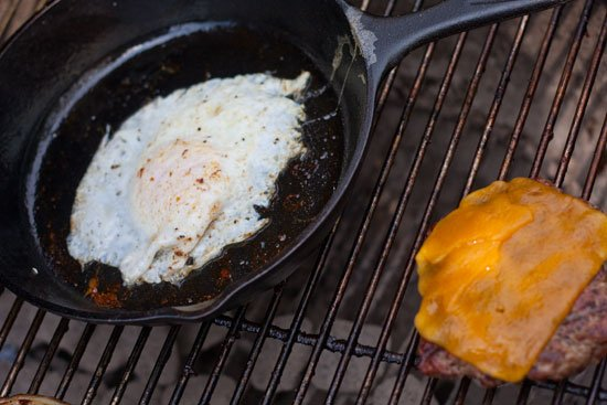 Bacon cheeseburger with a runny egg and fried onions.