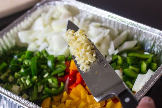 Chopping up vegetables with garlic for pulled smoked chuck roast