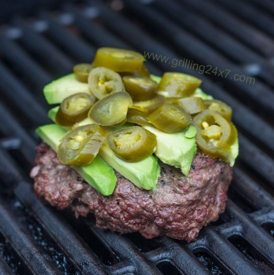 Burger with avocado and jalapeno peppers sitting on the grill - grilling24x7.com